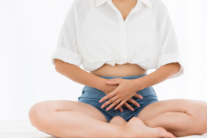 girl sitting cross legged with her hands on her stomach
